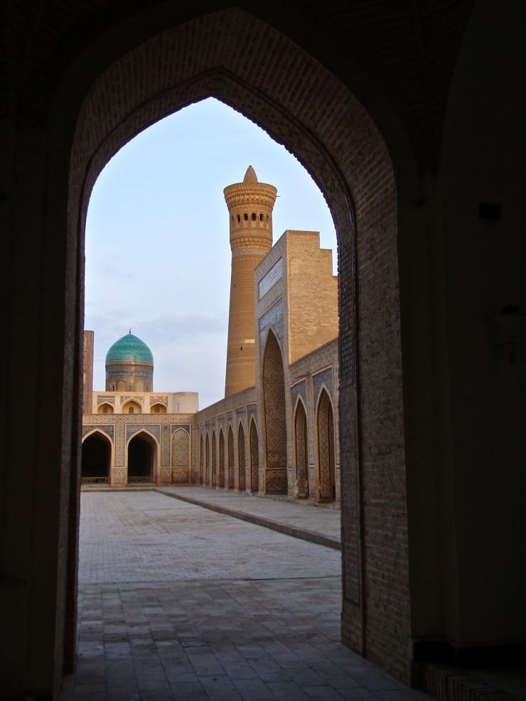 "Bukhara has a gritty, inhabited feel to it: people walk freely through occasionally crumbling medieval monuments, groceries in hand, while shop keepers hawk wares from under the domes of ancient bazaars.  With no tourists about in mid-winter, we were able to wander undistracted through the madrases, mausoleums, and mosques.  Here, the Po-i Kaylan (""Foot of the Great"") complex, showing the minaret of the Kaylan mosque and the turquoise dome of the Mir-i Arab Madrasah."