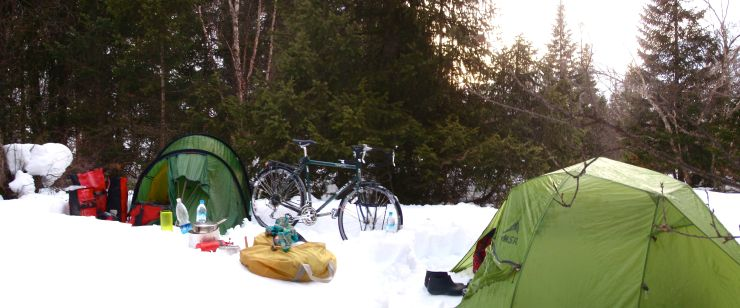 In the shadow of spruce, the snow is deep.  Work-hardening a tent platform, usually the province of winter ski trips, felt novel on a bike trip.